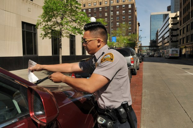 Noushue Cha, a parking enforcement officer in St. Paul, issues a parking ticket to a car parked at an expired meter in St. Paul on Thursday, May 10, 2018. Cha has been working for the city of St. Paul issuing tickets to cars parked at expired meters since January. Technology has changed the way traffic officer pass out tickets. With the use of an ipad in their car, traffic officers can log on and see which cars are parked at meters that have expired. On Thursday, May 10, 2018, Cha was out checking cars on Kellogg Blvd and Wabasha Street, areas that he patrols. Cha averages about 35 tickets a day. Cost of an expired meter is $36.00 in St. Paul. (Ginger Pinson / Pioneer Press)