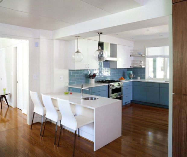 Architect Chris Snowber and designer Christie Leu were inspired to do a blue kitchen in this mid-century modern renovation. There are brightly colored, gloss-finished cabinets and glass tiles in blue. (Stacy Zarin Goldberg)