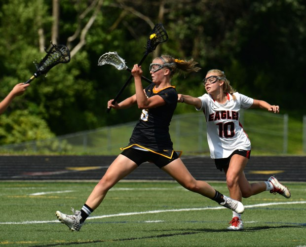 Apple Valley's Molly Moynihan (5) tries to pass the ball under defensive pressure from Eden Prairie's Reese Hugdahl (10) during the championship game of the State Girls' Lacrosse Tourament in Chanhassen on Saturday, June 16, 2018. Apple Valley won, 11-10. (Neal Lambert / Pioneer Press)