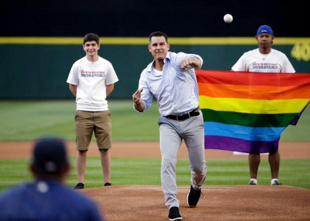 Billy Bean, Major League Baseball vice president of Social Responsibility & Inclusion, throws out the ceremonial first pitch to Seattle Mariners' Felix Hernandez before a baseball game between the Mariners and Milwaukee Brewers Friday, Aug. 19, 2016, in Seattle. The Mariners were celebrating LGBTQ Pride Night at the ballpark. (AP Photo/Elaine Thompson)