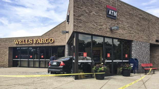 Officers work the scene where a car drove into an entrance of a Wells Fargo bank, Thursday, June 21, 2018, at 33rd Avenue and Third Street North in St. Cloud, Minn. Authorities say the incident was not intentional and likely due to driver error when the person was parking. One person in the car suffered non-life threatening injuries. (Jordyn Brown/St. Cloud Times via AP)