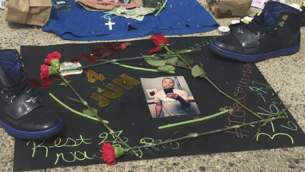 A memorial has been set up Monday, June 25, 2018, in a north Minneapolis alley where a black man was shot and killed by Minneapolis police. Authorities say Thurman Blevins Jr., 31, had a gun and was shot by officers on Saturday, June 23, 2018, after a foot chase. (AP Photo/Youssef Rddad)