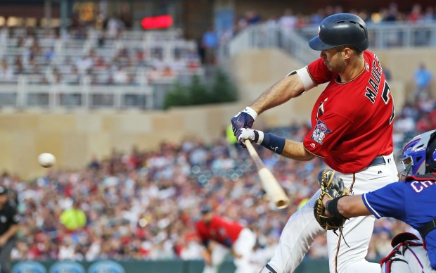 Minnesota Twins' Joe Mauer hits an RBI double off Texas Rangers' pitcher Mike Minor during the sixth inning of a baseball game Friday, June 22, 2018, in Minneapolis. (AP Photo/Jim Mone)