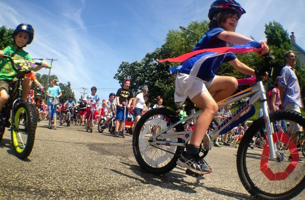 Children bring up the rear of the parade in bicycles decorated in patriotic colors in the St. Anthony Park 4th of July Parade in St. Paul on July 4, 2014. After the parade the community gathered in Langford Park for more music and an all day festival. (Pioneer Press: Ben Garvin)
