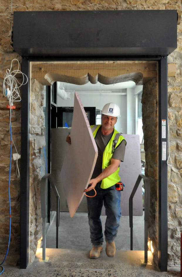 Mike Weeks, job superintendent from Zeman Construction, carries insulation through a door that connects the Feller Open Kitchen to the lobby at the Lora Hotel in downtown Stillwater on Thursday, May 24, 2018 as workmen move closer to the June 18, 2018 deadline of the hotel's opening. (Ginger Pinson / Pioneer Press)
