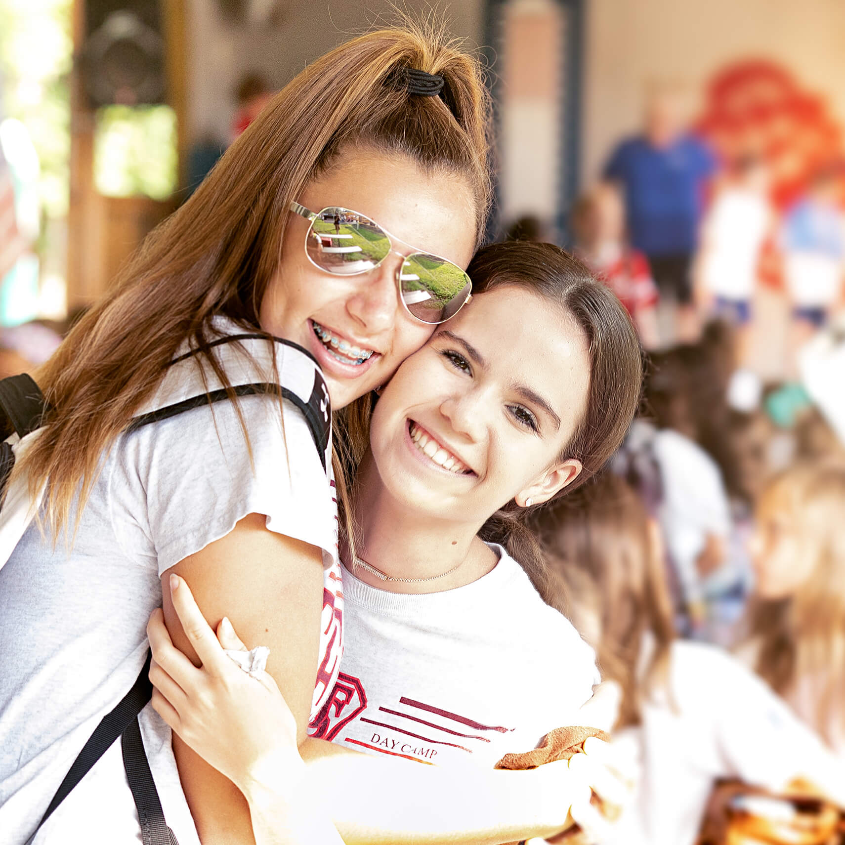 Two girls hugging and smiling.