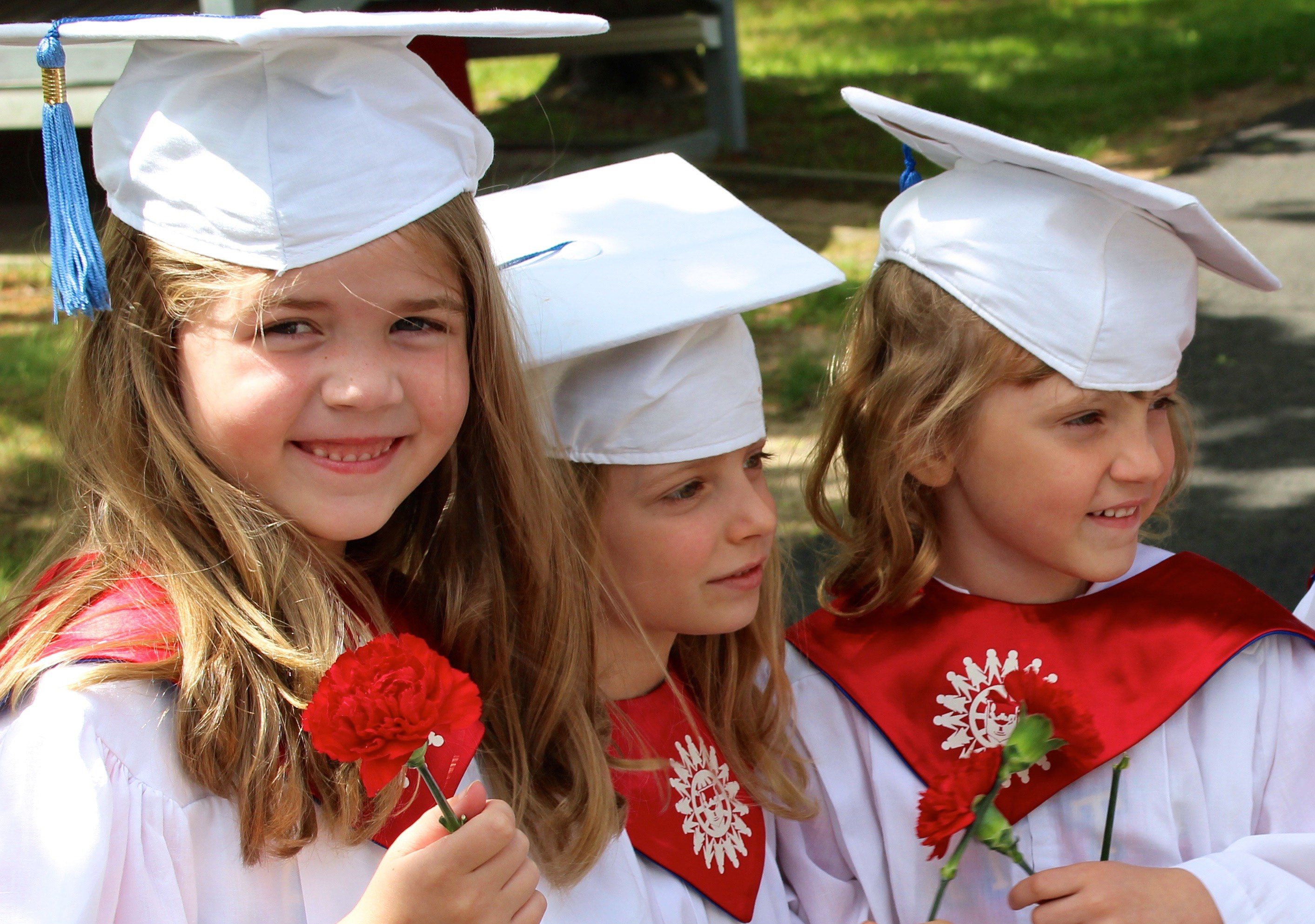 Toddlers in graduation outfits.