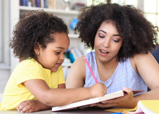 Teacher helping a student to write.