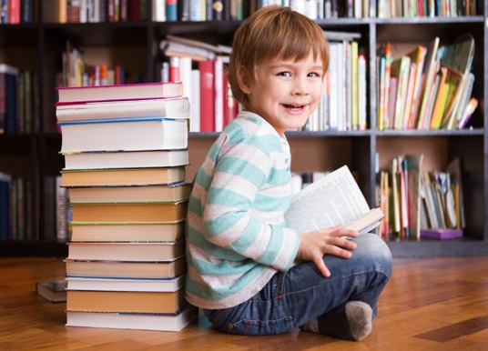 Boy toddler reading a book in a library.