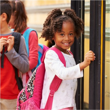 Young student getting on a bus.