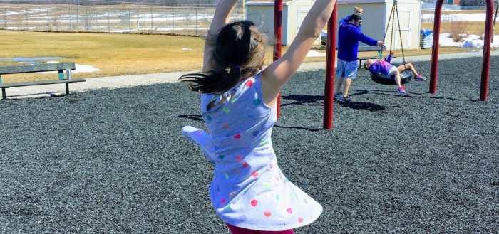 My daughter spinning around on playground