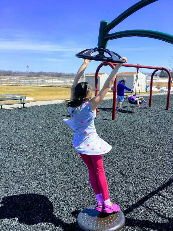 My daughter spinning around on playground