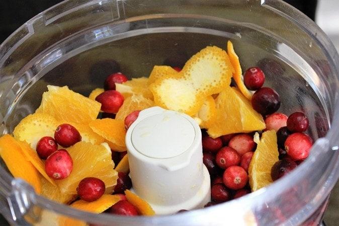 Orange, cranberries, sugar ready to process