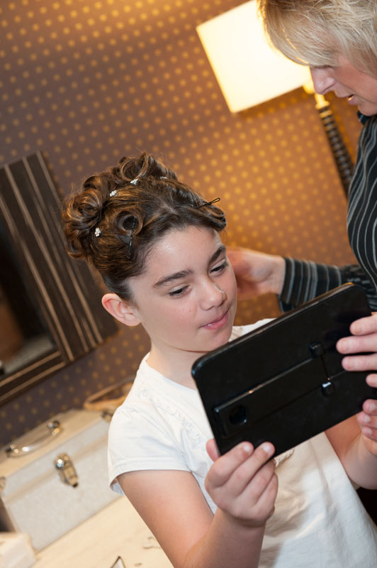 Wedding hair and make up tips-Bridesmaid getting her wedding hair and make up done and checking in the mirror.