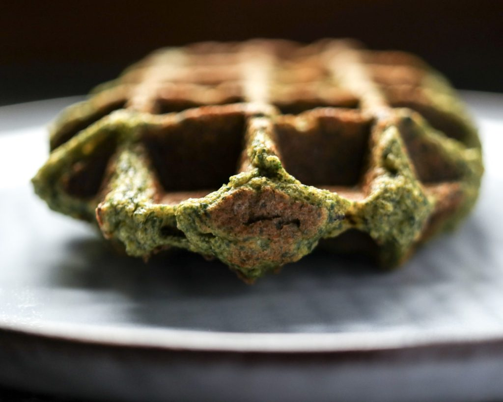 single sweet potato and spinach waffle on a light plate