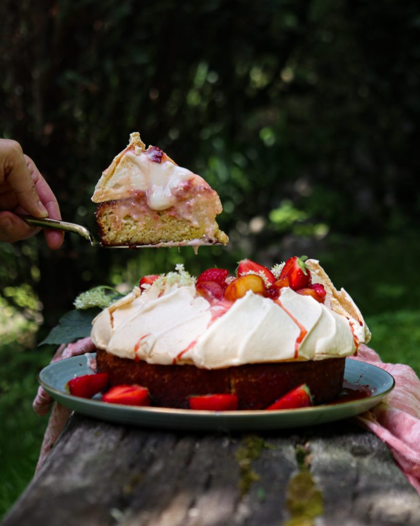 decadent saffron rice cake with pavlova crown on a green plate