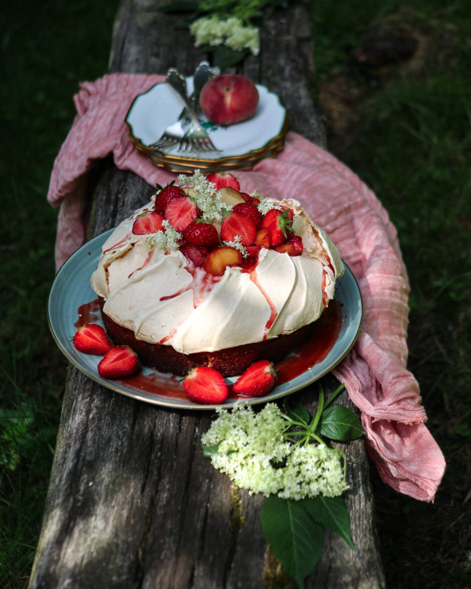 Saffron rice cake with pavlova crown on a green plate on a wooden bank