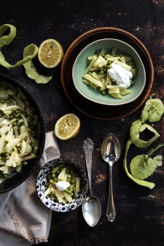 kohlrabi and peas with coconut milk and ginger in a green bowl with ingredients around