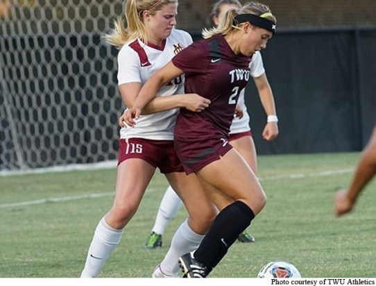 Midfielder Chelsea Martin #2 blocks a West Texas A&M soccer player from stealing the ball.