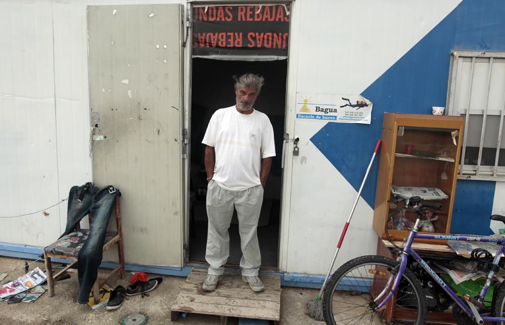 Enrique posa bajo la puerta de la caseta en la que vive, en uno de nuestros primeros encuentros. Agosto de 2013