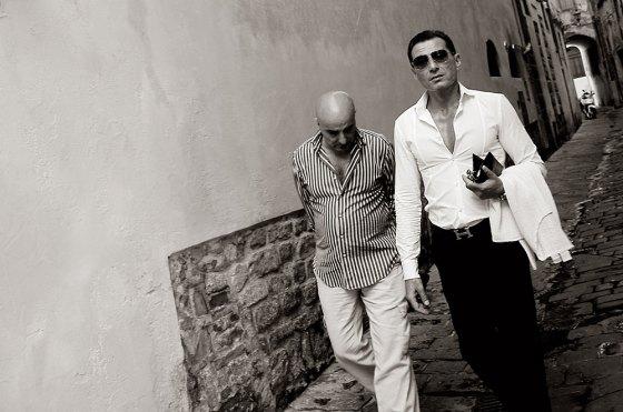 Un tipo que parece un gigoló y me mira raro junto a otro que baja la mirada. En un callejón florentino.