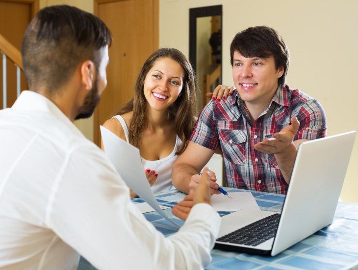 Smiling couple and salesman talking