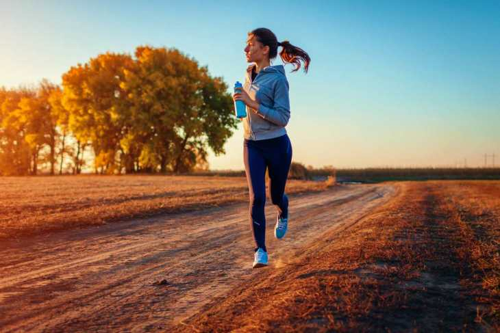 Woman running holding bottle of water in autumn field at sunset | Best Quick Workouts For Busy People Who Don't Have Much Time