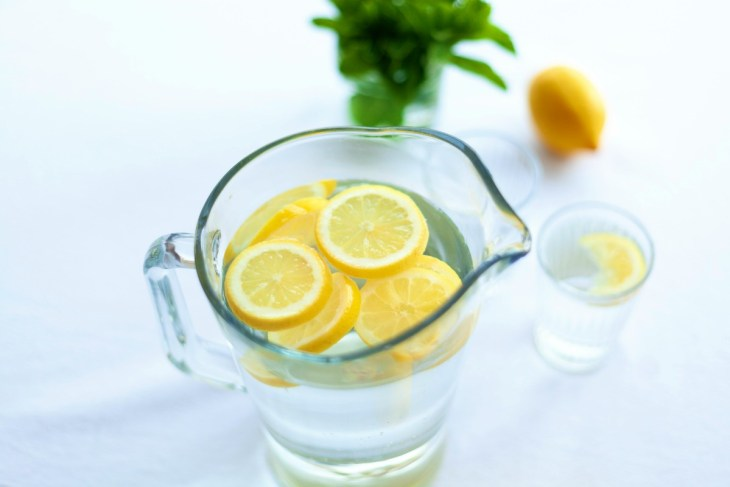 Sliced lemon fruit in glass pitcher | Ways To Drink More Water This Year
