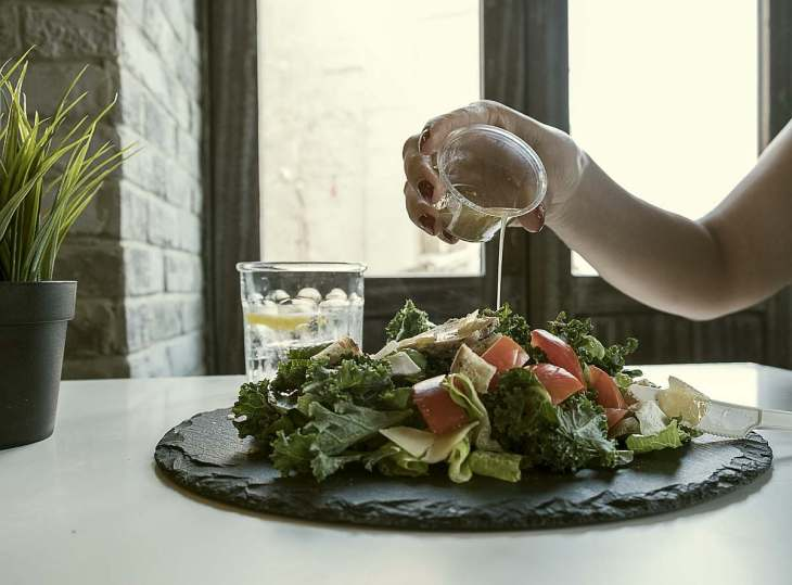 Person Pouring Dip on Vegetable Salad | Eat Healthier | Ways to Restore Your Body's pH Balance
