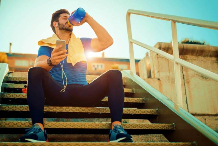 Tired fitness man sweating taking a break listening to music | Ways To Drink More Water This Year