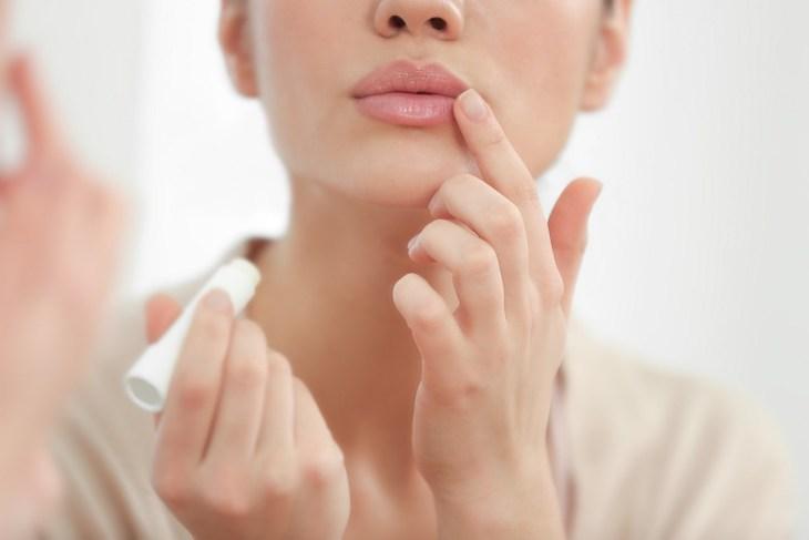 Woman applying lip balm | Surprising Benefits Of Baking Soda