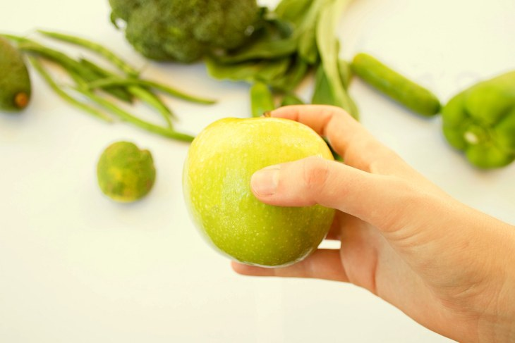 Holding apple on vegetable background | Why Should You Wash Fresh Produce with Alkaline Water?