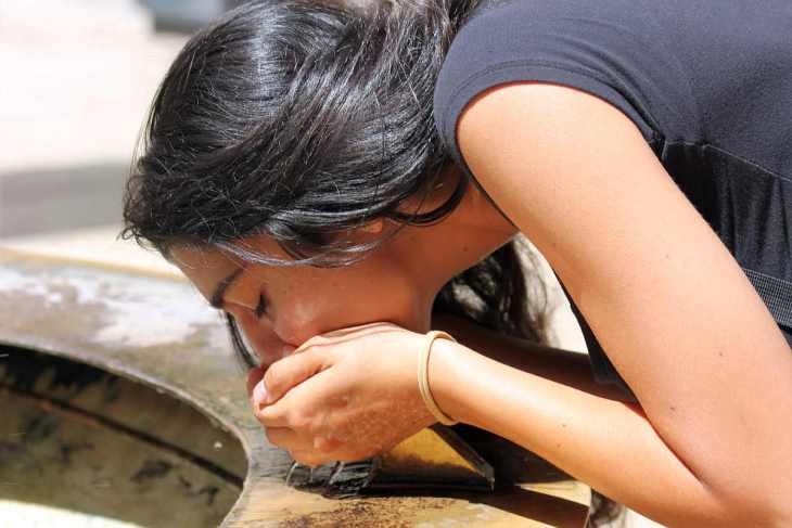 Girl with black hair drinking water | Is it Safe to Drink from a Public Water Fountain?