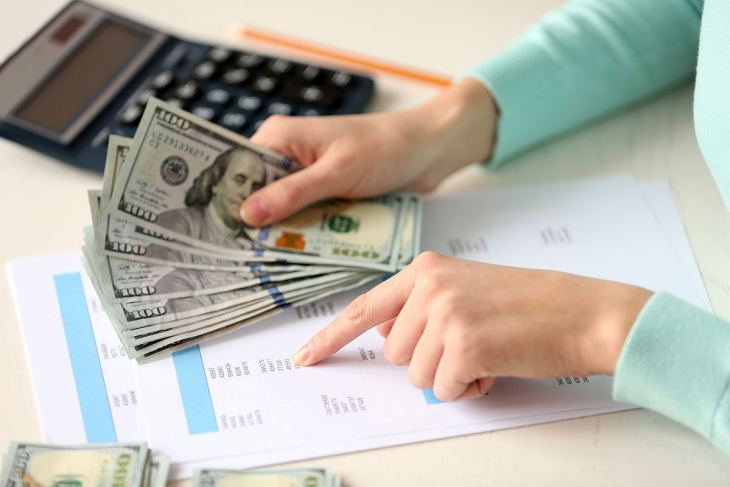 Woman counting money table   Reverse Osmosis Process: How Does It Work?