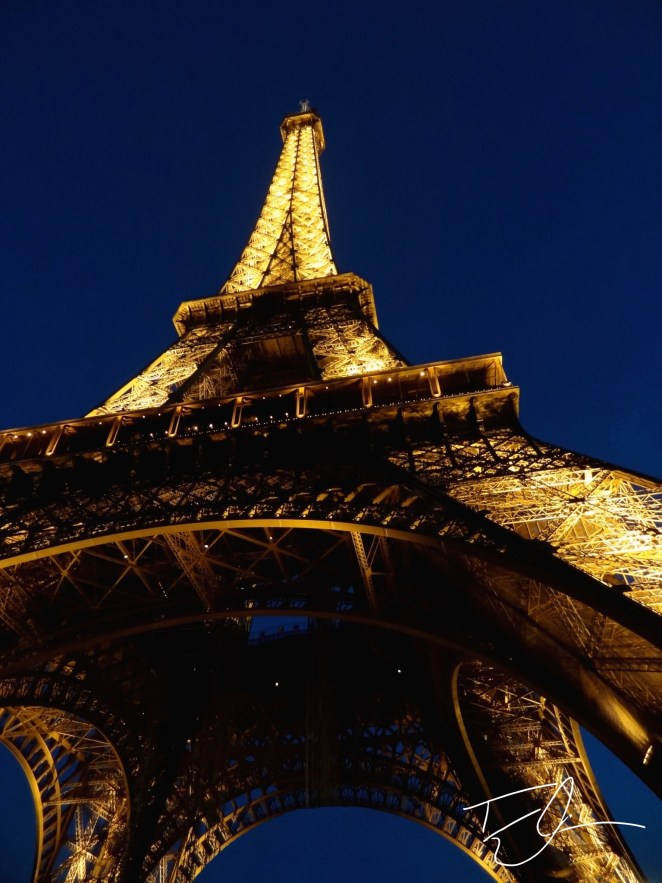 Looking up at Eiffel Tower at night in Paris, France