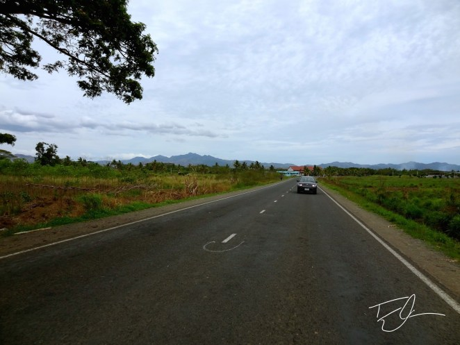 View of a Fijian Roadway from the back of a pickup truck taxi. By Tyler Cramer