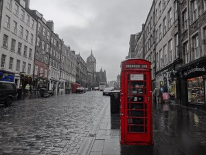 Looking down a gloomy street in Edinburgh Scotland contrasted with a bright red telephone booth