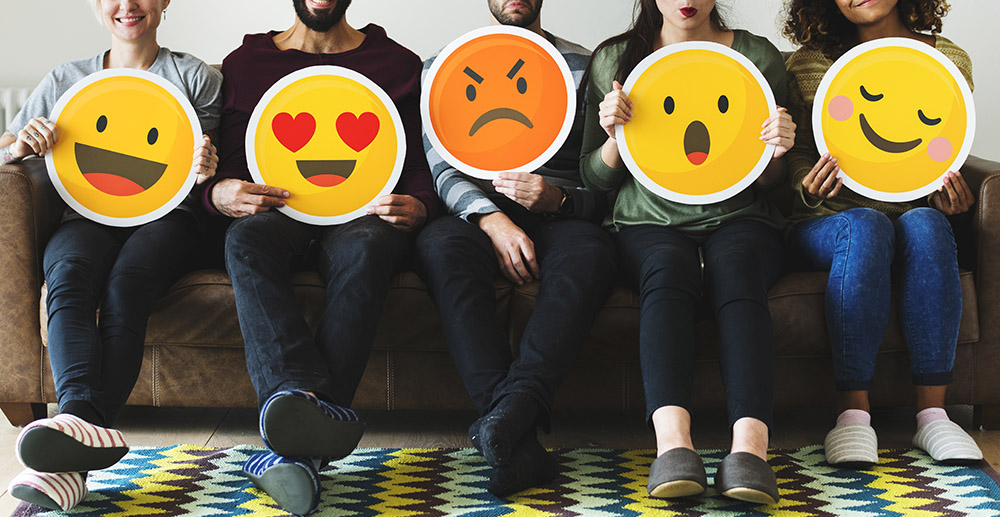 Group of diverse people holding emoticon icons how retailers use social media