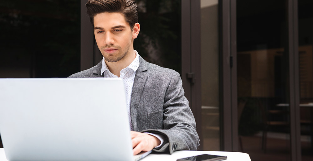 Focused young businessman on laptop computer