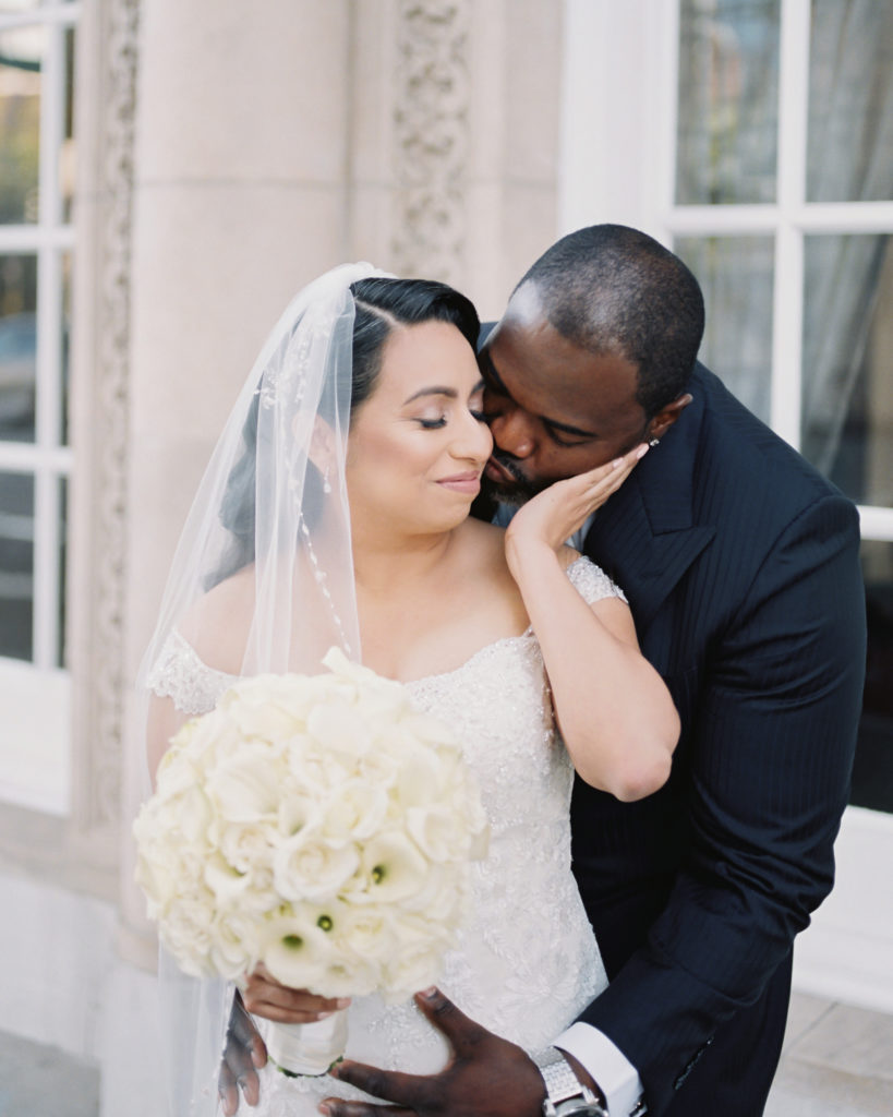 a groom kisses his bride before their wedding at The Westin San Jose