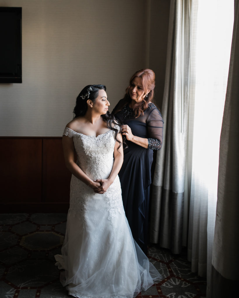 a bride's mother helps her dress for her wedding at The Westin San Jose