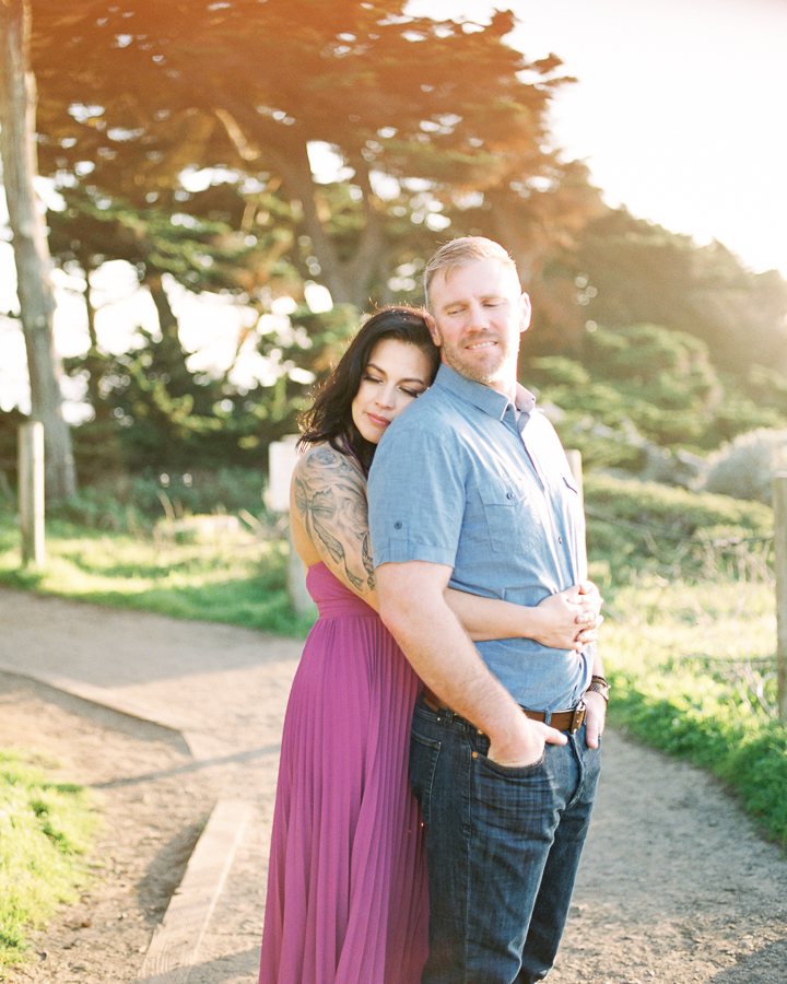 a couple in love during sunset engagement photos at Sutro Baths