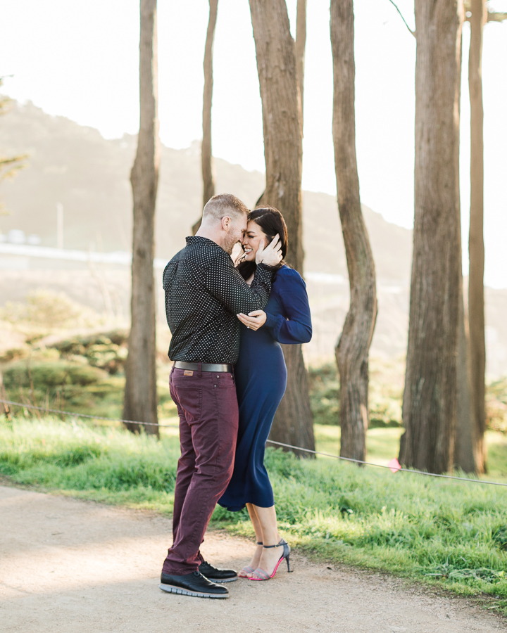 a couple cuddles during their engagement photos at Sutro Baths