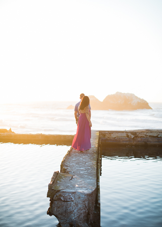 a couple walks along the bath walls during engagement photos at Sutro Baths