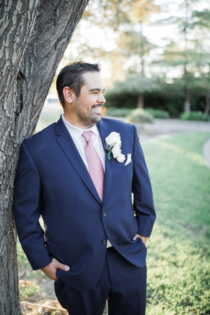 groom poses for photos during his intimate estate wedding