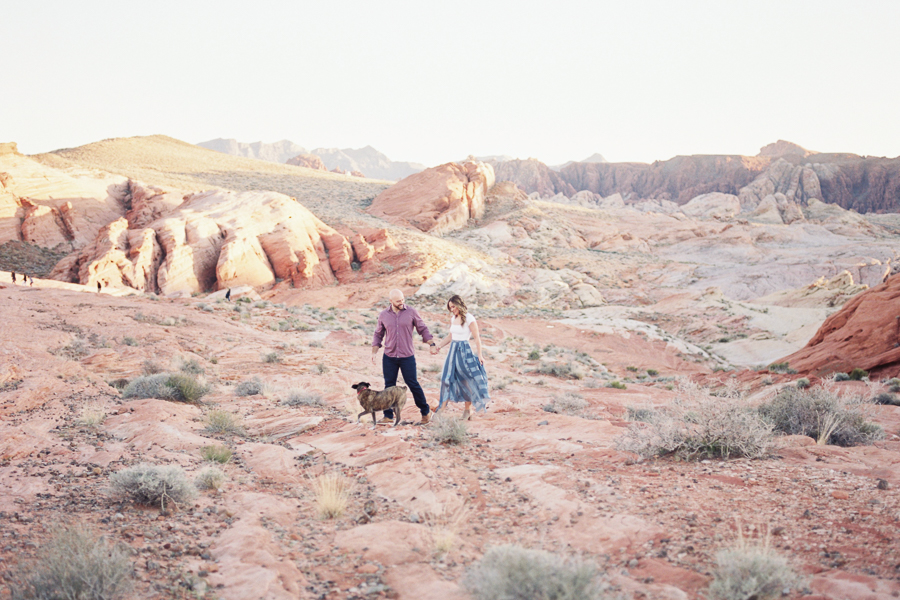 a couple and their dog run through the desert during their Valley of Fire engagement session