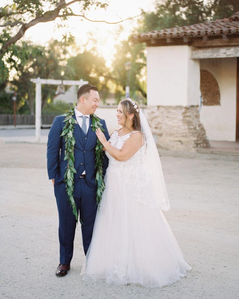 bride and groom with wedding leis at their wedding at Jardines de San Juan