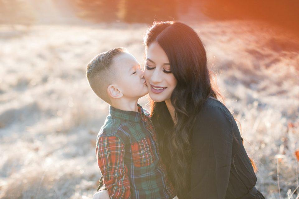 son gives mom a kiss during family photos at Santa Teresa Park