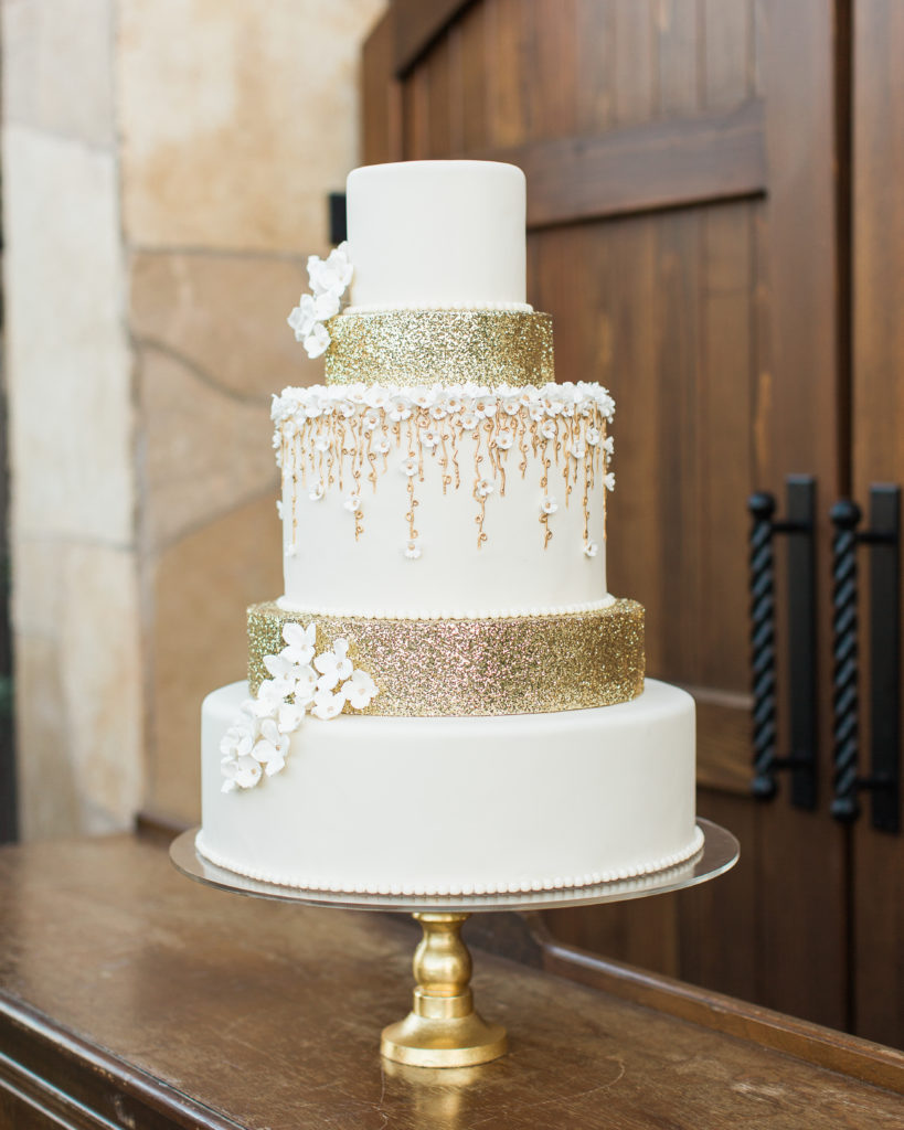 a gold and floral themed wedding cake by Something Sweet Bakery