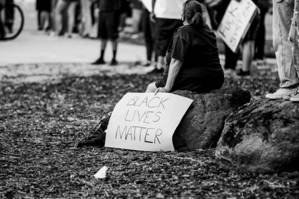 person holding black lives matter sign during protest